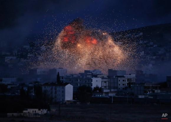 Espeso humo y las llamas de un ataque aéreo por la subida de la coalición liderada por Estados Unidos en Kobani, Siria, visto desde una colina en las afueras de Suruc, en la frontera entre Turquía y Siria, Lunes, 20 de octubre de 2014. Kobani, también conocido como Ayn árabe, y sus alrededores, ha estado bajo asalto por los extremistas del grupo Estado Islámico desde mediados de septiembre y está siendo defendida por combatientes kurdos. (AP Photo / Lefteris Pitarakis)