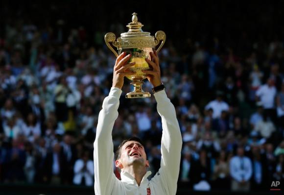 Novak Djokovic de Serbia sostiene el trofeo tras vencer a Roger Federer de Suiza en los individuales masculinos final en el All England Lawn Tennis Championships en Wimbledon, Londres, el domingo 6 de julio de 2014. (Foto AP / Ben Curtis)