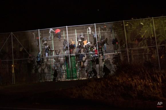Migrantes subsaharianos escalar una valla metálica que separa Marruecos y el enclave español de Melilla, por la mañana temprano el miércoles 28 de mayo de 2014. Varios cientos de inmigrantes africanos pagan la valla fronteriza de alambre de púas en el enclave del norte de África de España de Melilla con muchos la gestión para llegar al otro lado, mientras que decenas más fueron rechazados por la policía marroquí y española. Durante el asalto a la frontera antes del amanecer, gritos de dolor y ruidos de la gente de ser golpeado podían oírse ya que la policía de ambas partes trataron de impedir que decenas de los migrantes subsaharianos de entrar en la ciudad de Marruecos. (AP Photo / Santi Palacios)