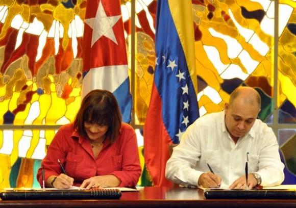 Firma de acuerdos entre Cuba y Venezuela, por la parte venezolana Nancy Pérez Sierra (I), ministra del Poder Popular para la Salud, y por la parte cubana, Roberto Morales Ojeda, ministro de Salud Publica ,durante la ceremonia de clausura de la XV Sesión de la Comisión Intergubernamenta entre estos dos paises, en el Palacio de la Revolución, el 13 de diciembre de 2014. AIN FOTO/Marcelino VAZQUEZ HERNANDEZ