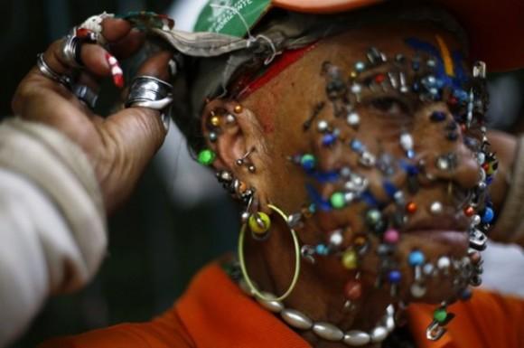 Un fanático de la selección brasileña que se desempeña como personal de limpieza de las calles de Brasil muestra su colección de piercings en su cara en Belo Horizonte, en julio. / Foto: elmeme.me