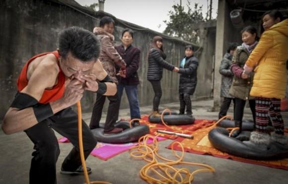 En Chengdu, China, Nie Yongbing infla neumáticos soplando aire por su nariz, mientras que algunas personas se paran sobre ellas. / Foto: elmeme.me