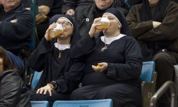 Canadá: dos mujeres vestidas de monjas beben cerveza mientras observan un partido de curling / Foto: elmeme.me