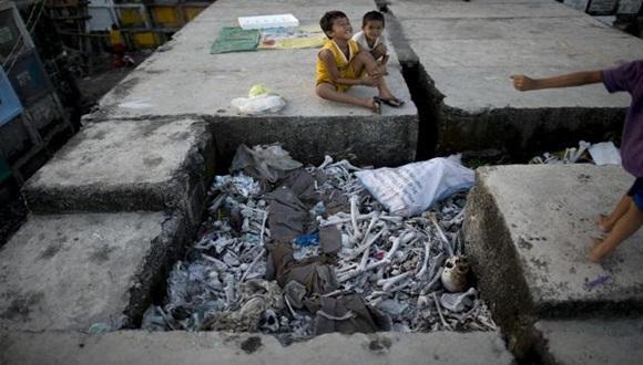 Varios niños juegan junto a huesos humanos en el cementerio público Navotas, de Manila, donde viven / Foto: AFP.