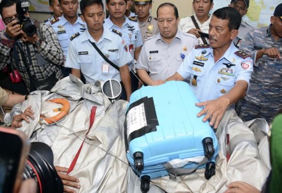 El comandante del 1er Comando Operativo de la Fuerza AÈrea de Indonesia, mariscal Dwi Putranto, derecha, muestra partes de aviÛn y un maletÌn que fueron hallados flotando en aguas cerca del sitio donde desapareciÛ el vuelo 8501 de AirAsia, el martes 30 de diciembre de 2014. (Foto AP/Dewi Nurcahyani)