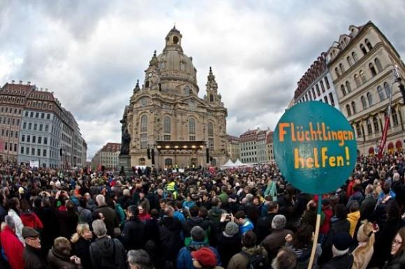 """Un cartel que decía """"Ayuda a los refugiados!"""" se puede ver en primer plano, mientras miles de personas participan en una manifestación con el tema """"Por Dresde, para Sajonia - convivencia en el sentido de una conciencia global, la humanidad y el diálogo"""" el 10 de enero de 2015, de frente a la Frauenkirche (Iglesia de nuestra Señora) en Dresde, Alemania del Este. La manifestación fue organizada como respuesta al movimiento anti-islámica Pegida, que tiene previsto reunirse de nuevo el lunes 12 de enero de 2015. Los analistas esperan que las filas de Pegida se hinchen por miles siguiente violencia yihadista sangrienta de esta semana en Francia. AFP PHOTO / DPA / ARNO BURGI +++ GERMANY OUT (Photo credit should read ARNO BURGI / AFP /"""