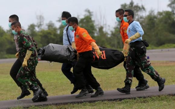 Funcionarios de la Agencia Nacional de B˙squeda y Rescate (BASARNAS) cargan con el cuerpo de vÌctima del accidente del vuelo 8501 de AirAsia, desde un helicÛptero a su llegada al aeropuerto de Pangkalan Bun, en Indonesia, el 3 de enero de 2015. (Foto AP/Tatan Syuflanai)