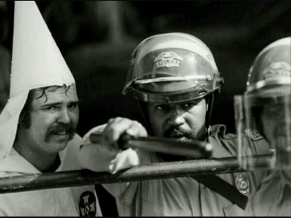 Oficial afroamericano protegiendo a un miembro del Ku Klux Klan de los manifestantes