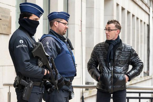 Policías belgas interrogan a un ciudadano a la entrada de un edificio de gobierno en Bruselas, en el marco de una redada antiterrorista. Foto: AP