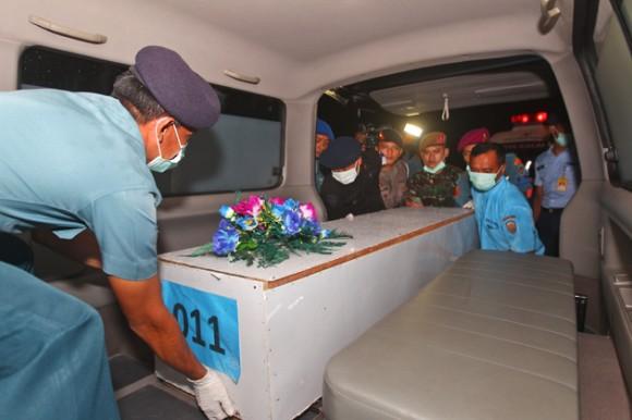 Militares indonesios colocan un ataud con los restos mortales de un pasajero del aviÛn de AirAsia accidentado dentro de una ambulancia luego de que llegaron a la base aÈrea y naval de Juanda, en Surabaya, Java oriental, Indonesia, el 2 de enero de 2015. (Foto AP/Firdia Lisnawati)
