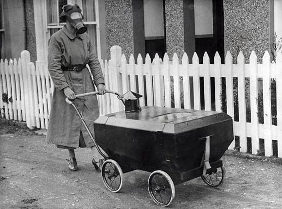 Una mujer con un cochecito antigás para su hijo, Inglaterra, 1938.