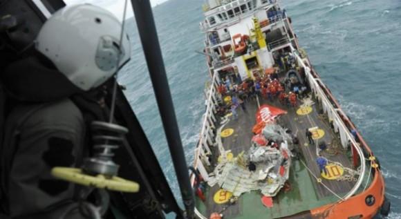 Momento en el que suben la cola del avión al barco de rescate indonesio. Foto:  EFE