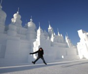 A man jumps to take his souvenir picture in front of large snow sculptures during the Harbin International Ice and Snow Festival in the northern city of Harbin