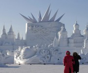 Visitors walk past large snow sculptures during the Harbin International Ice and Snow Festival in the northern city of Harbin