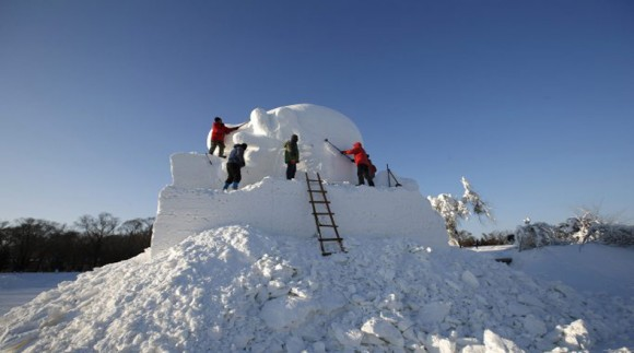 Workers carve a large snow sculpture during the Harbin International Ice and Snow Festival in the northern city of Harbin
