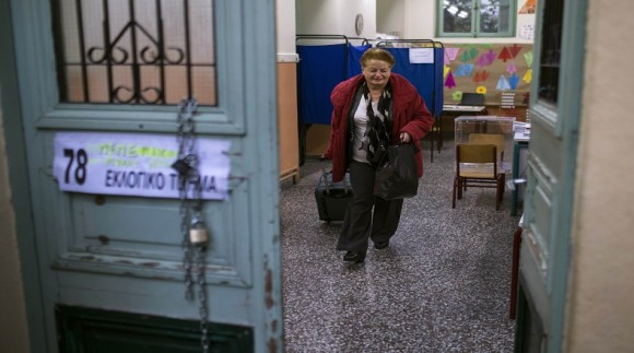 A woman exits a polling station after casting her ballot in an elementary school during Greece's parliamentary elections in Athens
