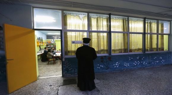 A Greek orthodox priest is seen outside a polling station at an elementary school during Greece's parliamentary elections in Athens