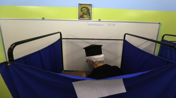 A Greek orthodox priest casts his vote in a booth during Greece's parliamentary elections, at an elementary school in Athens