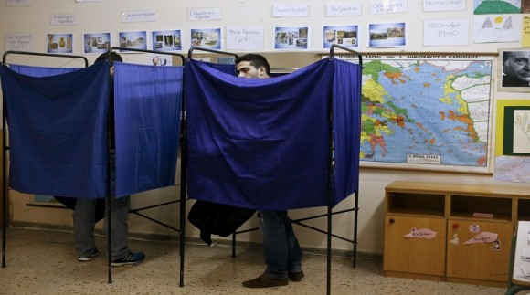 A man casts his vote in a booth during the Greek parliamentary elections in Athens