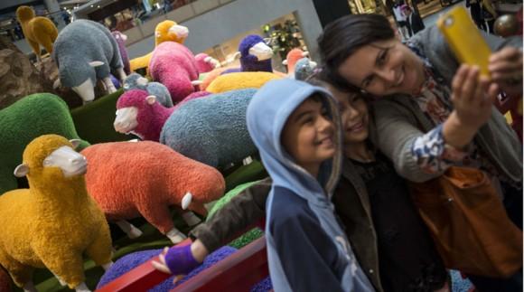 Personas se toman una fotografía frente a una instalacción con ovejas coloridas colocada para dar la bienvenida al Año de la Cabra, en un centro comercial, en Hong Kong, en el sur de China, el 18 de febrero de 2015. (Xinhua/Lui Siu Wai) (rhj)