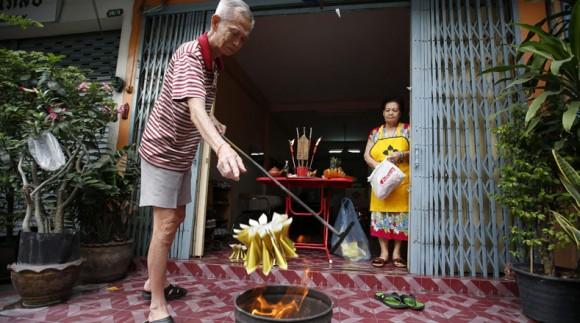 """Dinero de papel, llamado """"dinero espiritual"""", arde en un cubo durante el ritual tradicional de una familia tailandesa de etnia china con la creencia de que irá a sus antepasados a la entrada de su casa en Bangkok (Tailandia) hoy, miércoles 18 de febrero de 2015. EFE/Barbara Walton"""