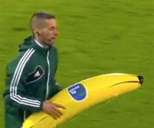 El cuarto árbitro retira el plátano hinchable lanzado por los seguidores del Feyenoord a Gervinho.