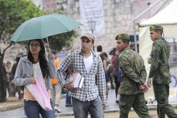 Una pareja  se protege del agua en la Fortaleza San Carlos de La Cabaña, sede principal de la XXIV Feria Internacional del Libro, durante la llegada de las lluvias de un frente frio a La Habana, Cuba, el 18 de febrero de 2015.  AIN FOTO/Roberto  MOREJÓN RODRÍGUEZ