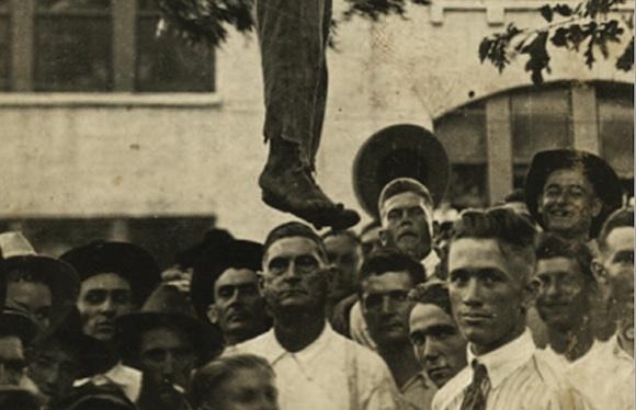 Hombres y niños posan debajo del cuerpo de Lige Daniels poco después de que fuera linchado el 3 de agosto de 1920, en Center, Texas.