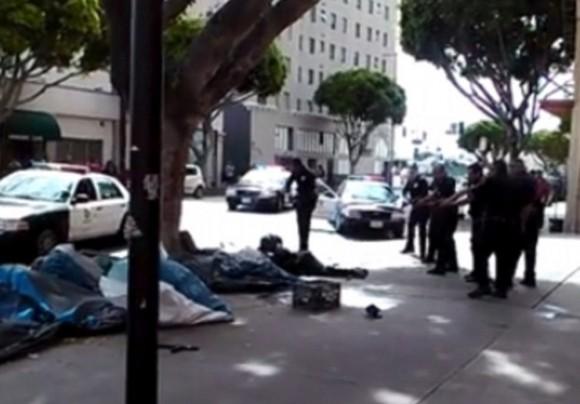 África yace en el suelo, frente a él, los oficiales de policía que le dispararon. Captura de video.