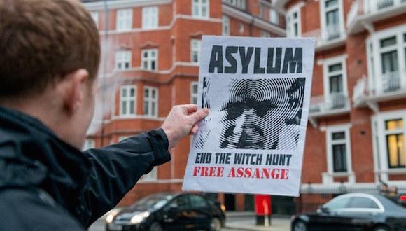 Un simpatizante de Julian Assange, sostiene un cartel frente a la embajada de Ecuador en Reino Unido, en el marco del cumplimiento de los mil días al interior de la embajada, en el centro de Londres
