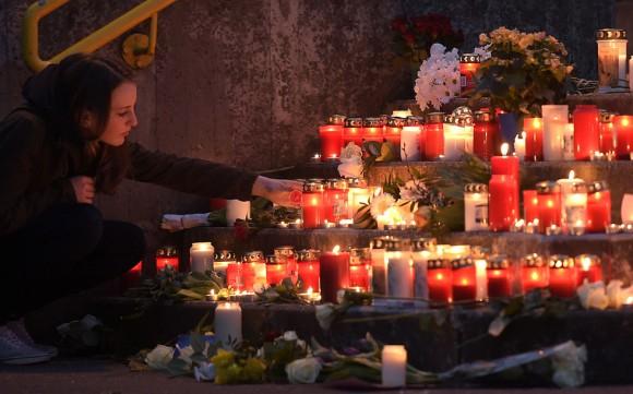 Una estudiante enciende una vela frente al Gimnasio Joseph-Koenig en Alemania. Foto: Martin Meissner