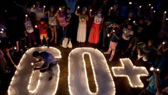 Varias personas encienden unas velas durante la iniciativa ecologista 'La Hora del Planeta' el 28 de marzo de 2015 en la ciudad colombiana de Cali (AFP | Luis Robayo)