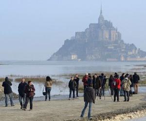 Varias personas esperan la subida de la marea en el Mont Saint Michel, en Francia. Foto: AP.