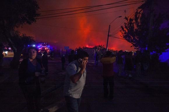 Varios residentes comienzan con la evacuaciÛn hoy, viernes 13 de marzo de 2015, despuÈs que el Gobierno de Chile declarÛ esta noche estado de emergencia para las ciudades de ValparaÌso y ViÒa del Mar, distante a 100 km. al oeste de Santiago, tras un gigantesco incendio forestal que ya ha destruido varias casas y se encuentra totalmente descontrolado. La informaciÛn fue entregada por el subsecretario del Interior, Mahmud Aleuy, quien precisÛ que ya se ha que se ha iniciado la evacuaciÛn de unas 16.000 personas. (Chile).EFE/Lucas Galvez
