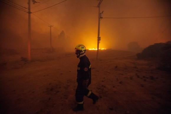 Un bombero camina cerca del fuego hoy, viernes 13 de marzo de 2015, despuÈs que el Gobierno de Chile declarÛ esta noche estado de emergencia para las ciudades de ValparaÌso y ViÒa del Mar, distante a 100 km. al oeste de Santiago, tras un gigantesco incendio forestal que ya ha destruido varias casas y se encuentra totalmente descontrolado. La informaciÛn fue entregada por el subsecretario del Interior, Mahmud Aleuy, quien precisÛ que ya se ha que se ha iniciado la evacuaciÛn de unas 16.000 personas. (Chile).EFE/Lucas Galvez