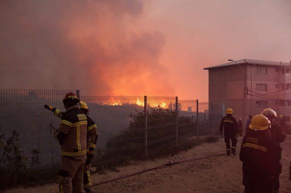 Varios bomberos observan el avance del fuego hoy, viernes 13 de marzo de 2015, despuÈs que el Gobierno de Chile declarÛ esta noche estado de emergencia para las ciudades de ValparaÌso y ViÒa del Mar, distante a 100 km. al oeste de Santiago, tras un gigantesco incendio forestal que ya ha destruido varias casas y se encuentra totalmente descontrolado. La informaciÛn fue entregada por el subsecretario del Interior, Mahmud Aleuy, quien precisÛ que ya se ha que se ha iniciado la evacuaciÛn de unas 16.000 personas. (Chile).EFE/Lucas Galvez