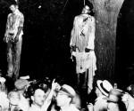 """En la fotografía se ve, parada debajo del árbol de arce de la plaza de los Tribunales de Marion, a la multitud de hombres blancos responsables del linchamiento de los jóvenes. Algunos sonríen a la cámara. Un hombre señala al cadáver de Abran """"Abe"""" Smith, colgado junto al de Thomas Shipp."""