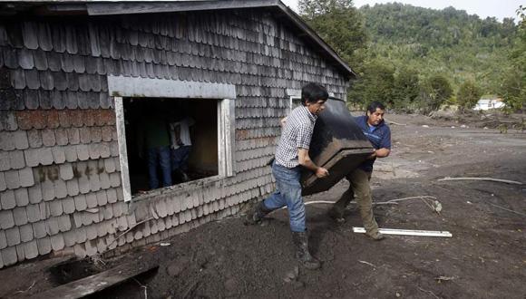 Dos hombres sacan objetos de una casa afectada por la erupción del volcán chileno Calbuco. Foto: EFE.