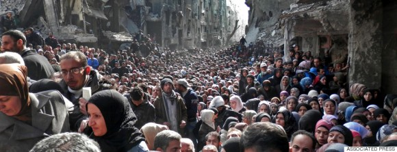 OR USE AS DESIRED, YEAR END PHOTOS - FILE - This picture taken on Jan. 31, 2014, and released by the UNRWA, shows residents of the besieged Palestinian camp of Yarmouk, queuing to receive food supplies, in Damascus, Syria. A United Nations official called on warring sides in Syria to allow aid workers to resume distribution of food and medicine in a besieged Palestinian district of Damascus. The call comes as U.N. Secretary General Ban Ki-Moon urged Syrian government to authorize more humanitarian staff to work inside the country, devastated by its 3-year-old conflict. (AP Photo/UNRWA, File)