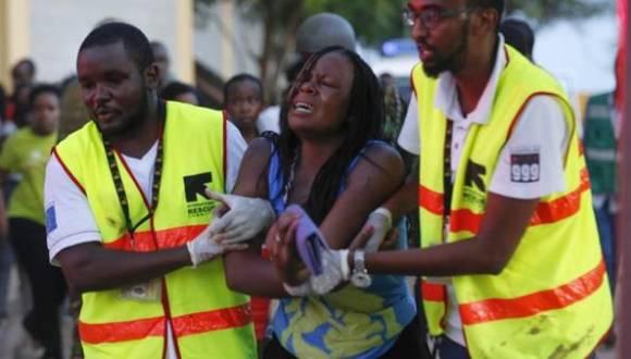 Dos sanitarios ayudan a una mujer que ha escapado de la Universidad de Garissa, en el este de Kenia tras el atentado terrorista. Foto: agencias.