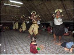 Grupo de danza con trajes tradicionales en el interior de una maneaba.
