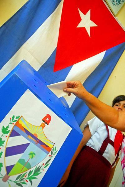 Elector deposita su voto en la urna custodiada por pioneros para elegir a su delegado a la Asamblea Municipal del Poder Popular, en Las Tunas, Cuba, el 19 de abril de 2015.     AIN  FOTO/ Yaciel PEÑA DE LA PEÑA