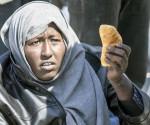 Una inmigrante enseña un trozo de pan en Calabria. Foto: EFE