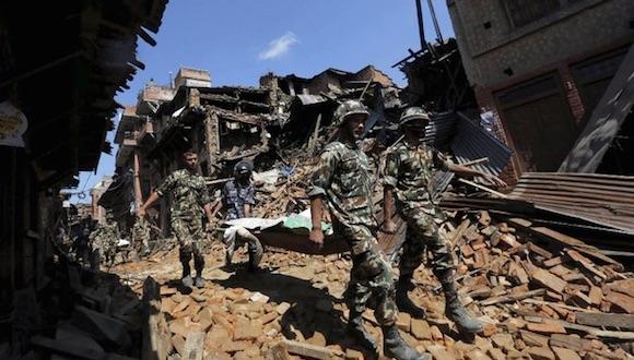 Soldados cargan un cuerpo encontrado entre los escombros que dejó el sismo en Nepal. Foto Reuters.