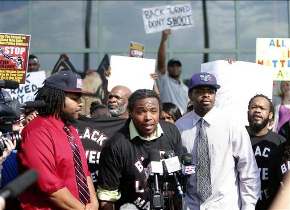 Muhiyidin D'baha (c) portavoz del moviemiento Black Lives Matters se dirige este 8 de abril a los medios durante la manifiestación en frente del Ayuntamiento de North Charleston en Carolina del Sur, EE.UU.
