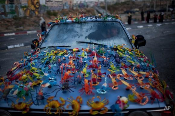 Imanes para la venta se muestran en el coche de un hombre palestino en el puesto de control de Kalandia, entre Jerusalén y la ciudad cisjordana de Ramallah, el 13 de agosto de 2010. (Foto AP / Bernat Armangue)