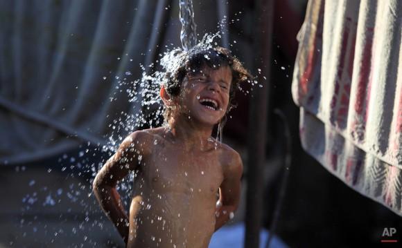 Naeema Abu Shaweesh, derrama agua sobre sus hijos fuera de su casa en la ciudad de Gaza. (Foto AP / Hatem Moussa)
