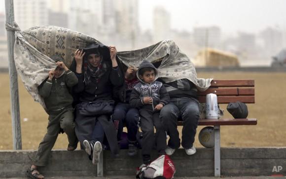Una familia palestina cubre a sí mismos de la lluvia en el puerto de Gaza, en la ciudad de Gaza, 15 de febrero de 2014. (Foto AP / Hatem Moussa)