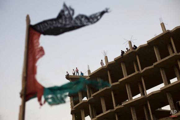 Los palestinos se reúnen en la azotea de un edificio en el que se detuvo la construcción y que fue bombardeado en enero de 2009 durante la ofensiva militar israelí en Beit Lahiya, norte de la Franja de Gaza el 16 de septiembre de 2011. (Foto AP / Bernat Armangue)