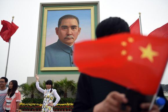 Asistentes a los actos del Primero de Mayo en la plaza de Tiananmen de Pekín se fotografían con el retrato de Sun Yat-sen, considerado el padre fundador de la China moderna.